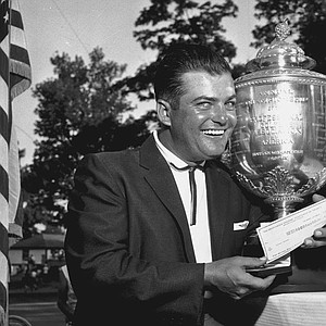 Golfer Lionel Hebert poses with his check and trophy after winning the PGA Championship on July 22, 1957 in Dayton, Ohio.