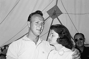 Arnold Palmer puts an arm around his wife, Winnie, after leaving the 18th green with a first round 67 in the National PGA Championship July 21, 1960 in Akron, Ohio. He clipped three strokes from par to take an early lead on the rest of the field at the Firestone Country Club.