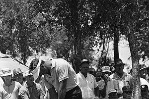 Golfer Arnold Palmer chips from the frog hair of the first green for an eagle 3 in the opening round of the PGA Championship, July 18, 1963, Dallas, Texas. A woman spectator in the gallery leans out to get a better view of the shot.