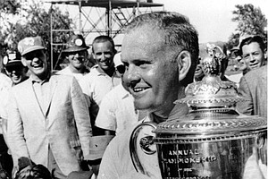 Golfer Jack Nicklaus holds up the Wanamaker trophy after winning the PGA championship in Dallas, Tex., on July 22, 1963. Seated left is Dave Ragan who was runner up.