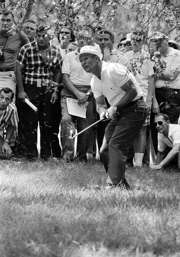 Arnold Palmer sports a hat for him a rare item on the golf course-as he watches flight of his ball after shooting from the rough on No. 2 hole in third round of PGA championship on July 18, 1964 in Columbus, Ohio. Arnie bogeyed the par 4 hole.