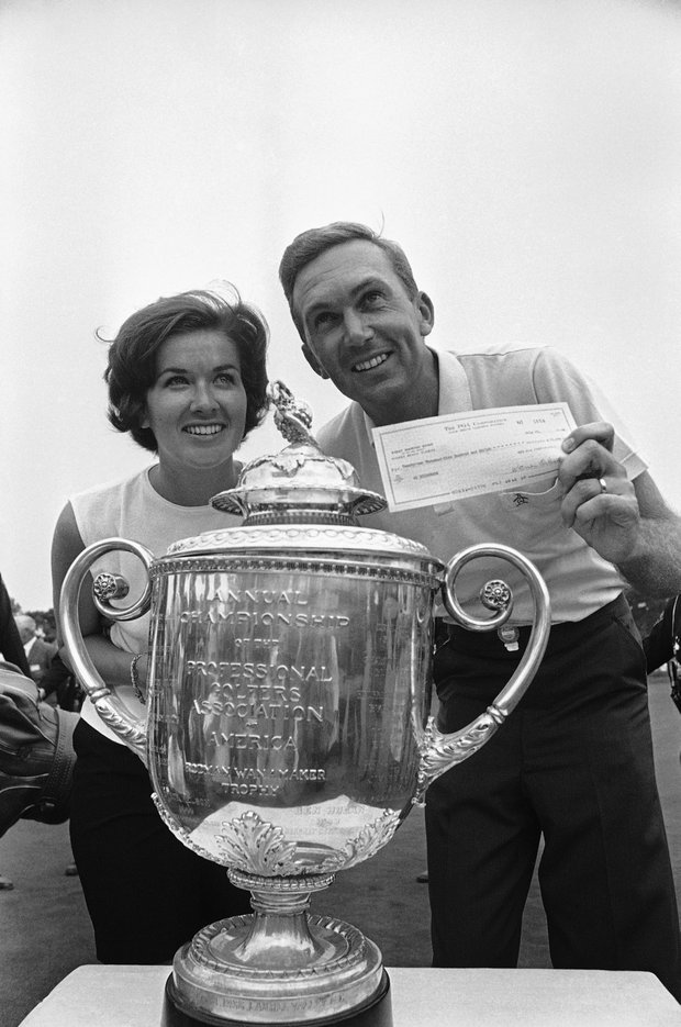 Golfer Al Geiberger poses with his wife, Lynn, and trophy after winning the PGA championships at the Firestone Country Club in Akron, Ohio, September 24, 1966.
