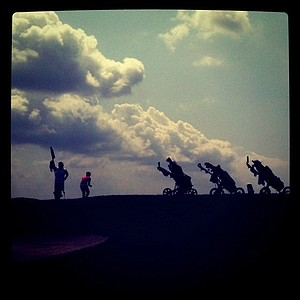 Players push carts are silhouetted along the green at hole No. 17.