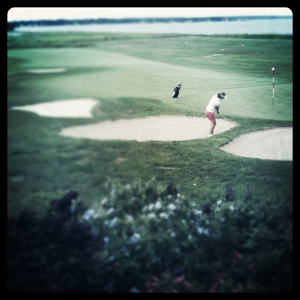 A player hits out of a bunker at No. 18.