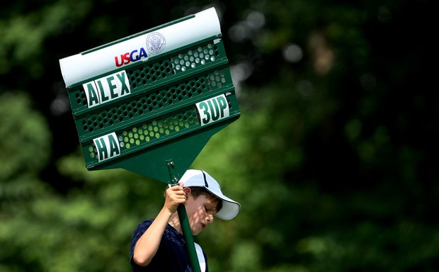 A standard bearer carries a sign around for the Cindy Ha and Marina Alex group during the Round of 64 at the U. S. Women's Amateur Championship at Rhode Island Country Club in Barrington, Rhode Island.