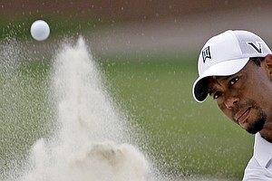 Tiger Woods hits out of a bunker on the fifth hole during a practice round for the PGA Championship golf tournament Tuesday, Aug. 9, 2011, at the Atlanta Athletic Club in Johns Creek, Ga.