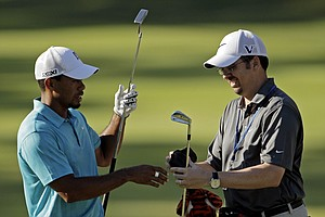 Caddie Bryon Bell helps Tiger Woods with a club on the 16th hole during a practice round for the PGA Championship golf tournament Wednesday, Aug. 10, 2011, at the Atlanta Athletic Club in Johns Creek, Ga.
