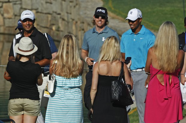 Fans watch as Tiger Woods, right, Hunter Mahan and Arjun Atwal, left, make their way to the 18th hole during a practice round for the PGA Championship golf tournament Wednesday, Aug. 10, 2011, at the Atlanta Athletic Club in Johns Creek, Ga.