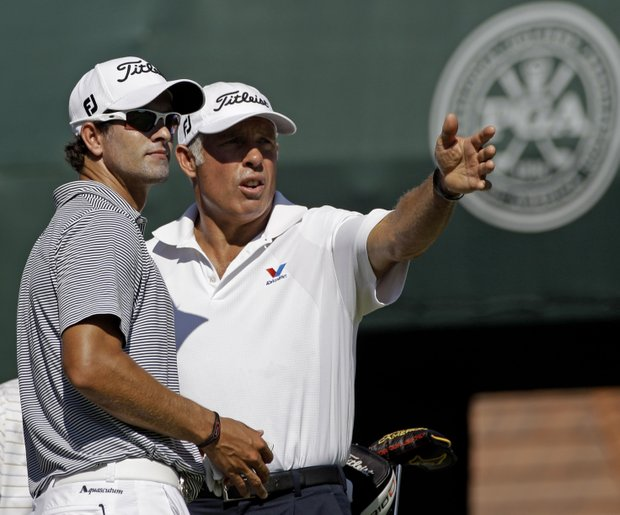 Adam Scott, of Australia, talks to caddie Steve Williams during a practice round for the PGA Championship golf tournament Wednesday, Aug. 10, 2011, at the Atlanta Athletic Club in Johns Creek, Ga.
