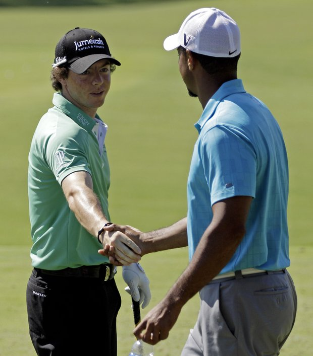 Tiger Woods, right, shakes hands with Rory McIlroy, of Northern Ireland, on the range at the PGA Championship golf tournament Wednesday, Aug. 10, 2011, at the Atlanta Athletic Club in Johns Creek, Ga.