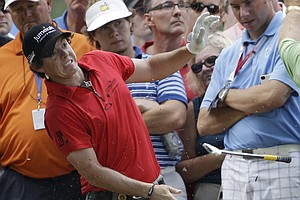 Rory McIlroy, of Northern Ireland, reacts as he loses his club after hitting a tree root on the third hole during the first round of the PGA Championship golf tournament Thursday, Aug. 11, 2011, at the Atlanta Athletic Club in Johns Creek, Ga.