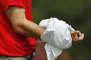 Rory McIlroy, of Northern Ireland, has his wrist wrapped in ice as he walks up to the eighth tee during the first round of the PGA Championship golf tournament Thursday, Aug. 11, 2011, at the Atlanta Athletic Club in Johns Creek, Ga. Mcllroy was injured when his club struck a tree root on the third hole.
