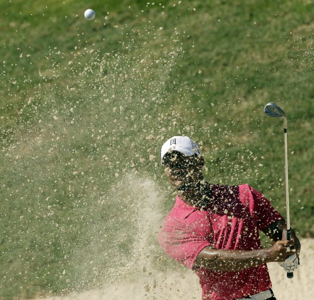 Tiger Woods hits out of a bunker on the 16th hole during the first round of the PGA Championship golf tournament Thursday, Aug. 11, 2011, at the Atlanta Athletic Club in Johns Creek, Ga.