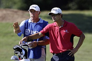 Adam Scott, of Australia, talks to caddie Steve Williams on the first hole during the first round of the PGA Championship golf tournament Thursday, Aug. 11, 2011, at the Atlanta Athletic Club in Johns Creek, Ga.