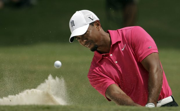 Tiger Woods hits out of a bunker on the ninth hole during the first round of the PGA Championship golf tournament Thursday, Aug. 11, 2011, at the Atlanta Athletic Club in Johns Creek, Ga.