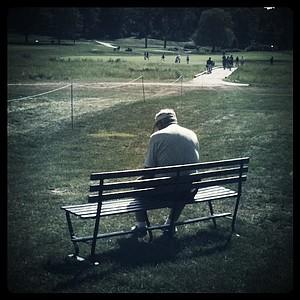 A lone spectator takes a break near the 11th hole.