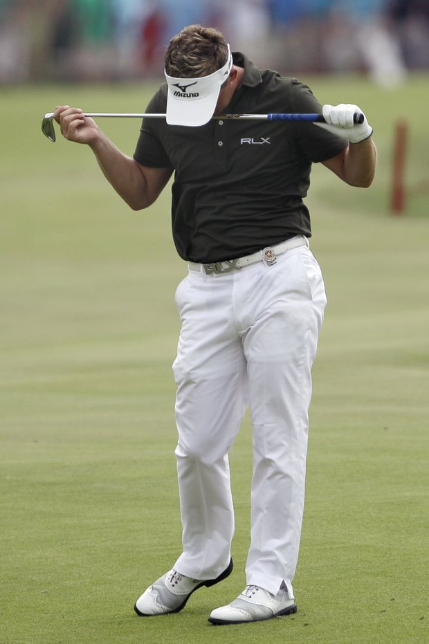 Luke Donald, of England, reacts after hitting into the water on the 18th hole during the third round of the PGA Championship golf tournament Saturday, Aug. 13, 2011, at the Atlanta Athletic Club in Johns Creek, Ga.