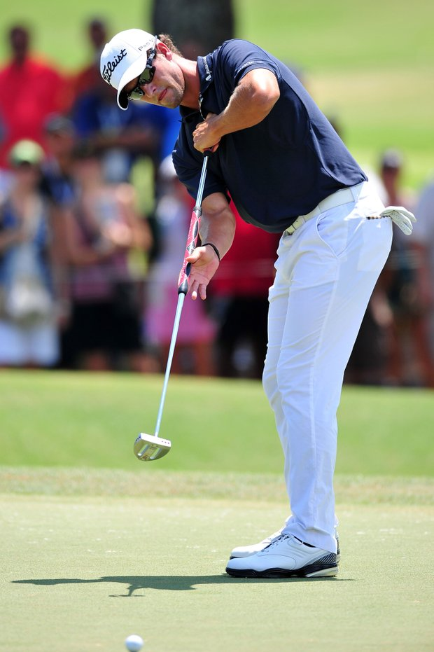 Adam Scott of Australia putts the ball on the first green during the final round of the 93rd PGA Championship at the Atlanta Athletic Club on August 14, 2011 in Johns Creek, Georgia.