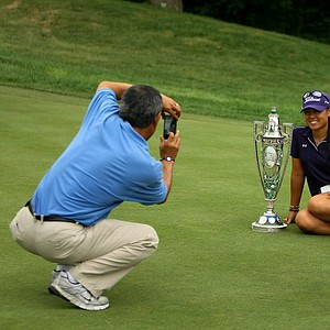 Danielle Kang smiles for her dad, K. S. Kang, as he takes a picture with his cell phone while posing for Golfweek and USGA photographers after winning the 2011 U. S. Women's Amateur Championship at Rhode Island Country Club in Barrington, Rhode Island.
