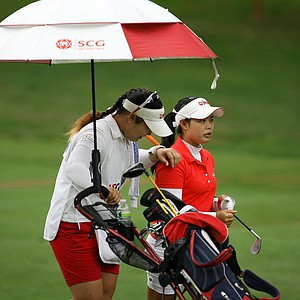 Moriya Jutanugarn, right, with her caddie/sister and USGA champion, Ariya Jutanugarn, share a laugh at No. 14 during the final round at the U. S. Women's Amateur Championship at Rhode Island Country Club in Barrington, Rhode Island. Jutanugarn birdied the hole.