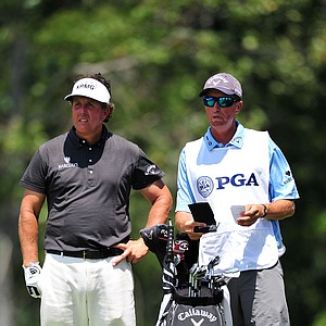 Phil Mickelson (L) and his caddie Jim Mackay (R) look on from the second tee during the final round of the 93rd PGA Championship at the Atlanta Athletic Club on August 14, 2011 in Johns Creek, Georgia.