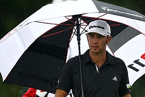 Dustin Johnson stands under an umbrella on the eighth tee box during the third and final round of The Barclays at Plainfield Country Club. Johnson won the event, which was shortened due to Hurricane Irene.