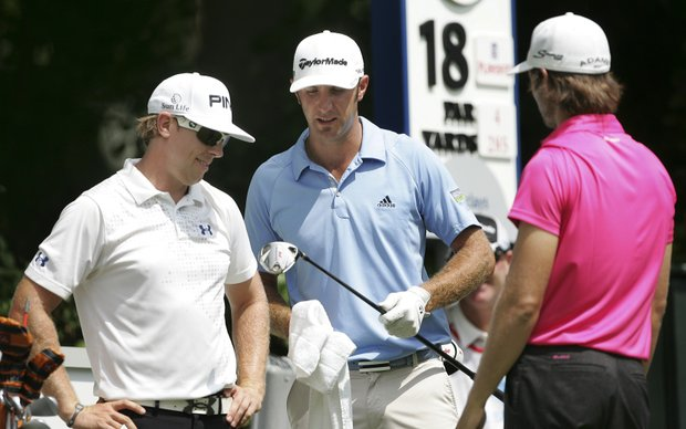 Dustin Johnson, center, shows his driver to Hunter Mahan, left, and Aaron Baddeley, right, of Australia before they teed off on the 18th hole during the second round of The Barclays golf tournament, Friday, Aug. 26, 2011, in Edison, N.J.
