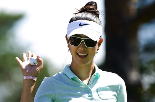 Michelle Wie from the United States waves to fans as she tees off on the first hole during the second round of the Canadian Open women's golf tournament at the Hillsdale Golf Club in Mirabel, Quebec, Friday, Aug. 26, 2011.