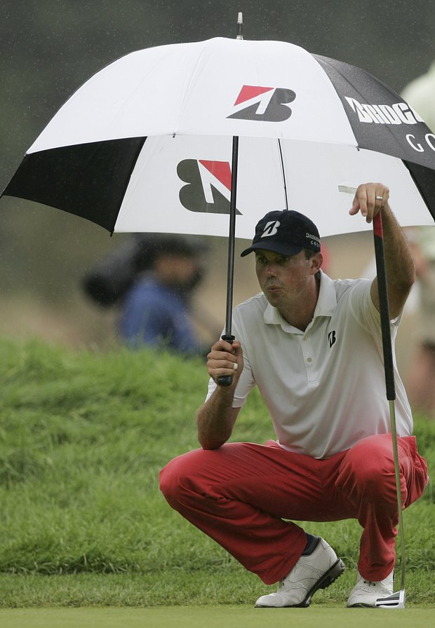 Matt Kuchar takes shelter under an umbrella while lining up his putt on the 14th green during the final round of The Barclays golf tournament Saturday, Aug. 27, 2011, in Edison, N.J.
