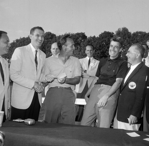 Harold Gallaway, left, head of an automobile dealers' organization, shakes hands with Arnold Palmer and presents him with a check for $25,000 for winning the Thunderbird tournament at the Westchester Country Club in Harrison, N.Y., June 16, 1963. Palmer won in a sudden death playoff over Paul Harney, right, who does not seem unhappy that he lost to the master who shot a par three on the first playoff hole after they tied the regulation 72 holes with 277 each.