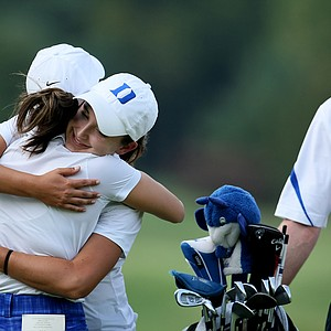 Duke's Lindy Duncan hugs her assistant coach Jeanne Cho, left, while head coach, Dan Brooks looks on after she defeated Alabama's Jennifer Kirby in a playoff. Duke as a team finished in seventh.