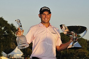 Bill Haas celebrates with the FedEx Cup and the Tour Championship trophy after defeating Hunter Mahan after three playoff holes at East Lake Golf Club in Atlanta on Sunday, Sept. 25, 2011.