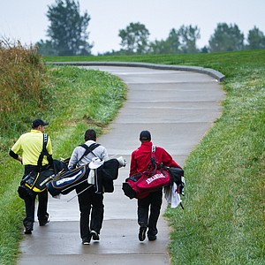 Players walk along the cart path during Monday's rain-soaked round at the Golfweek Conference Challenge.