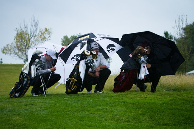 Players huddle from the elements on the No. 18 teebox while waiting for the fairway to clear during the second round of the Golfweek Conference Challenge.
