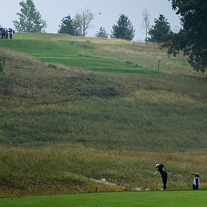 Players wait on the elevated teebox for OSU's Drew Page to hit his shot on the 18th at Spirit Hollow.
