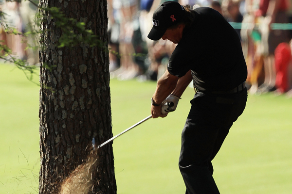 Phil Mickelson plays a shot from the pine needles on the 13th hole during the final round of the 2010 Masters.