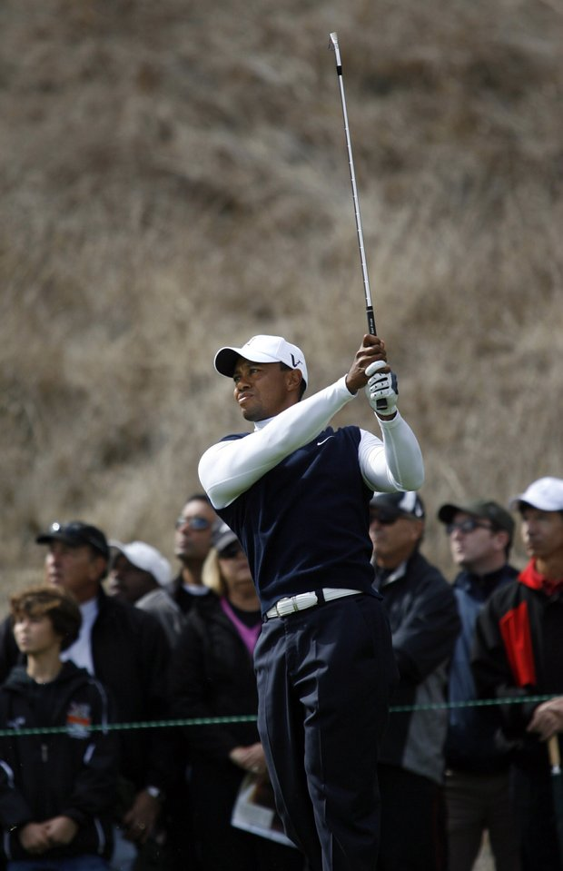 Tiger Woods tees off on the par-3 third hole at the first round of the Frys.Com Open