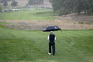Tiger Woods heads up the fourth hole as the rain falls during the first round of the the Frys.Com Open.
