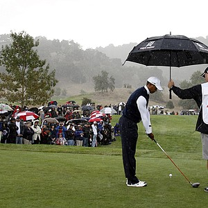 Tiger Woods gets an assist from his caddie Joe LaCava as rain falls during the first round of the Frys.Com Open.