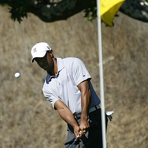 Tiger Woods hits a chip shot close to the hole on the 18th green during the second round of the Frys.Com Open.