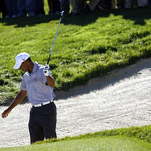 Tiger Woods reacts after hitting this bunker shot into another trap on the 13th hole at the second round of the Frys.Com Open.