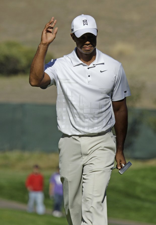 Tiger Woods waves to fans after making a birdie putt on the 11th hole during the third round of the Frys.com Open.