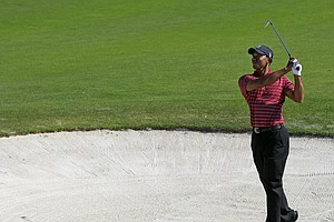 Tiger Woods hits from a fairway bunker on the 13th hole during the final round of the Frys.com Open.