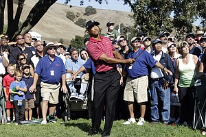 Tiger Woods chips to the green on the ninth hole during the final round of the Frys.com Open.