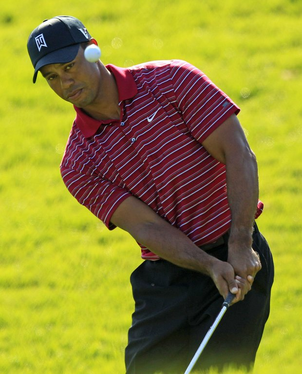 Tiger Woods chips to the green on the 13th hole during final round of the Frys.com Open.