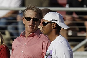 Hall-of-Fame quarterback John Elway, left, talks with golfer Tiger Woods, right, during the first quarter of an NCAA college football game between Stanford and Colorado on Saturday night.