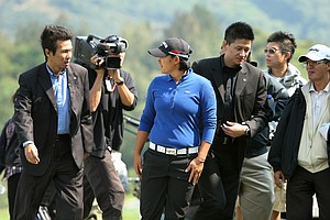 Yani Tseng is escorted by security as she practices on Tuesday prior to the 2011 Sunrise LPGA Taiwan Championship at Sunrise Golf and Country Club.