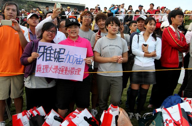 "Young fans from a local school hold a sign saying ""Go Yani"" during Thursday's round. The students attend a college in the area."