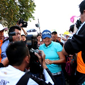 Yani Tseng is swarmed by fans as she leaves the scoring area on Thursday. She attempted to sign a few hats, but security whisked her away.
