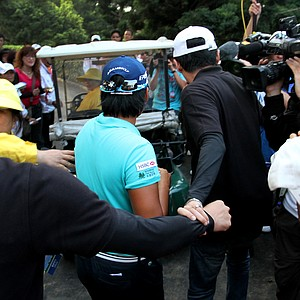 Yani Tseng is guided by her security to a waiting golf cart.